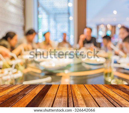 wood table and Chinese restaurant blur background with bokeh image .
