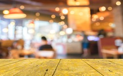 wood table and Coffee shop blur background with bokeh image.