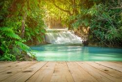 Wood table and Kuang Si waterfalls in Luang Prabang, Laos.