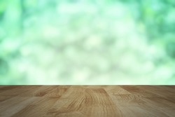 wood table background with abstract blurred soft light fresh green nature background, mock up for green eco environmental friendly product display. soft light tone image.