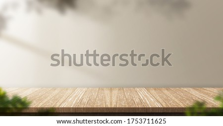 wood table background with sunlight window create leaf shadow on wall with blur indoor green plant foreground.panoramic banner mockup for display of product,warm tone lights