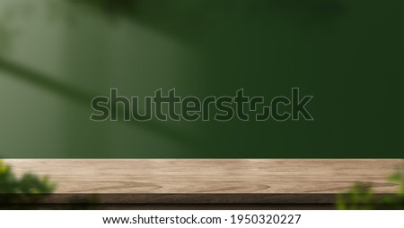 wood table green wall background with sunlight window create leaf shadow on wall with blur indoor green plant foreground.panoramic banner mockup for display of product.eco friendly interior concept