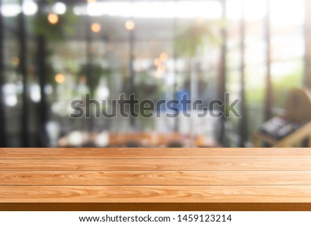 Wood table in blurry background of modern restaurant room or coffee shop with empty copy space on the table for product display mockup. Interior restaurant counter design concept.