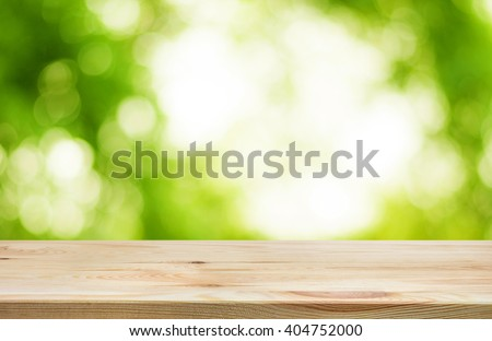 Wood table top and blur of  fresh green bokeh from garden background .For product display and natural concept