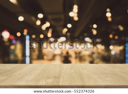 Wood table top and blurred bokeh cafe and restaurant background with vintage filter - can used for display or montage your products.