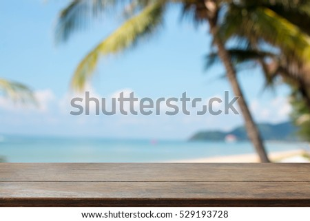 Wood table top and blurred summer beach and sky background. - can used for display or montage your products.