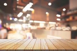 Wood table top background with blurred cafe and restaurant.