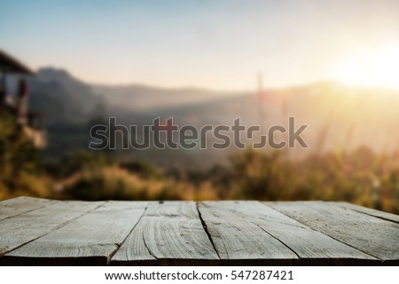 Wood table top in front of of trees in the forest. blur background image, for product display montage.
