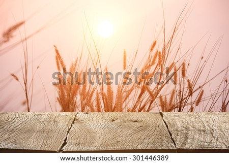 Wood table top on beautiful landscape image with grass flower at sunset background
