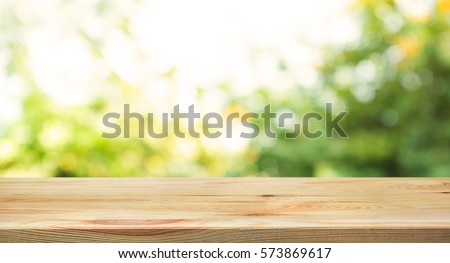 Wood table top on blur abstract green from garden in the morning background.For montage product display or design key visual layout
