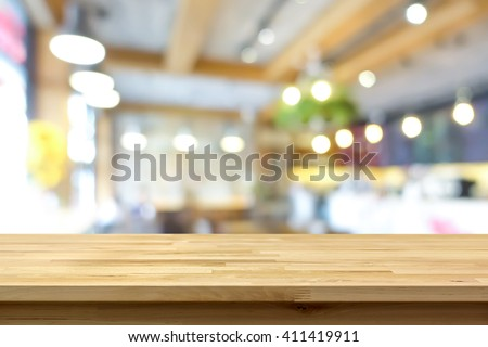 Wood table top on blur background of coffee shop (or restaurant) interior - can be used for display or montage your products