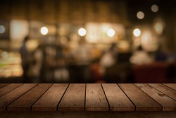 Wood table top on blur bokeh coffee shop or cafe restaurant background. Can be used for display or montage your products.