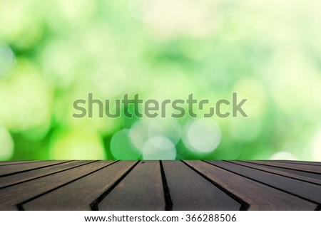 Wood table top on blur green abstract background - can be used for montage or display your products