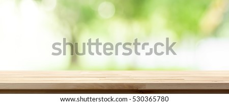 Wood table top on blur green background of trees in the park, panoramic banner - can be used for display or montage your products