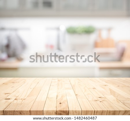 Photo of Wood table top on blur kitchen counter (room)background.For montage product display or design key visual layout.