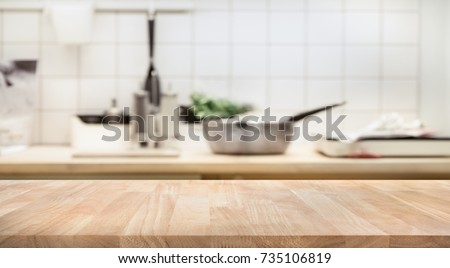 Photo of Wood table top on blur kitchen room background .For montage product display or design key visual layout.