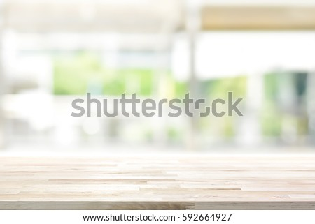 Wood table top on blur kitchen window background - can be used for display or montage your products (foods)