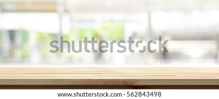 Wood table top on blur kitchen window background, panoramic banner - can be used for display or montage your products (or foods) #562843498