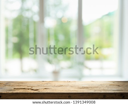 Wood table top on blur of window glass and abstract green from garden with city view in the morning background. For montage product display #1391349008