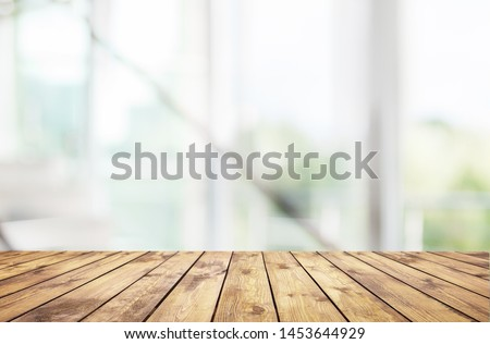 Wood table top on blur of window glass and abstract green from garden with city view in the morning background. For montage product display          - Image