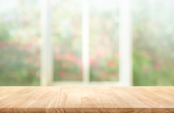 Wood table top on blur of window with garden flower background in morning.For montage product display or design key visual layout