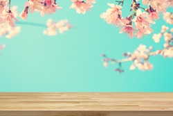 Wood table top on blur pink Sakura flower background, vintage tone - can be used for display or montage your products
