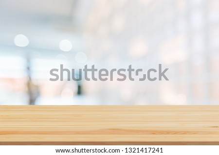 Wood table top on blur white glass wall background form office building.For montage product display and design key visual layout          - Image #1321417241