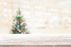 Wood table top on blur with bokeh christmas tree background with snowfall - can be used for display or montage your products.