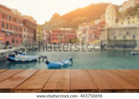 Wood table top on Blurred background of Manarola village on cliff rocks and sea at sunset.Seascape in Five lands, Cinque Terre ,Italy Europe.vintage tone color,can be used display your products