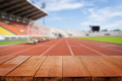 Wood table top on blurred background of Red running tracks in sport stadium  - can be used for display or montage your products