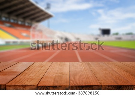 Wood table top on blurred background of Red running tracks in sport stadium  - can be used for display or montage your products #387898150