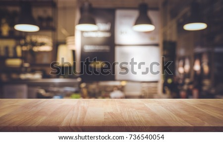 Wood table top on blurred of counter cafe shop with light bulb background.For montage product display or design key visual layout. #736540054