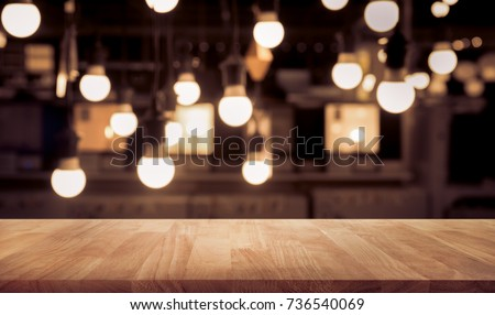 Wood table top on blurred of counter cafe shop with light bulb background.For montage product display or design key visual layout. #736540069