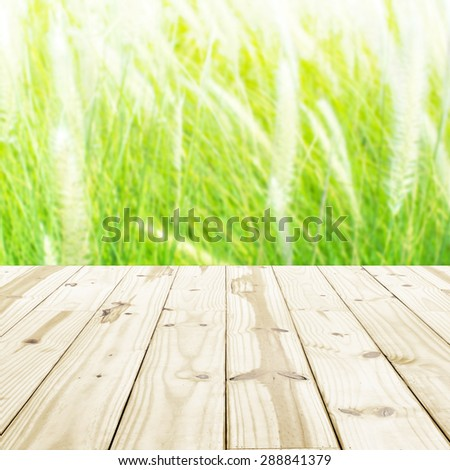 Wood table top on blurry grass flowers backgrounds.
