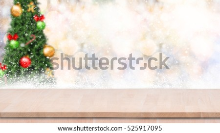 Wood table top on gold bokeh christmas tree background with snowfall.