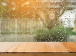 Wood table top on rain drops on clear window - can be used for display or montage your products