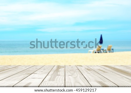 Wood table top on sea beach blurred in background  Empty table for display.