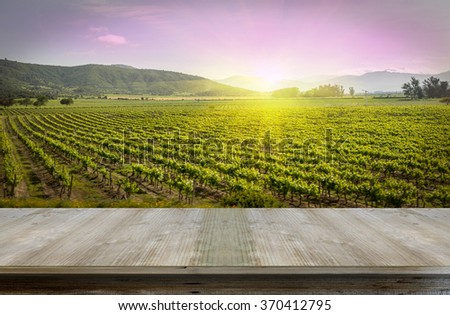 Wood table top on vineyard  background - vineyard wine scenery of pink sky with sun set on a vineyard winery landscape for winery industry background