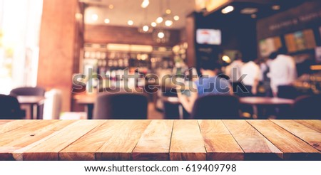 Wood table top with blur coffee shop,cafe background.For montage product display or design key visual layout
