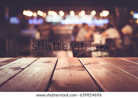 Wood table top with blur light bokeh in dark night cafe,restaurant background .Lifestyle and celebration concepts