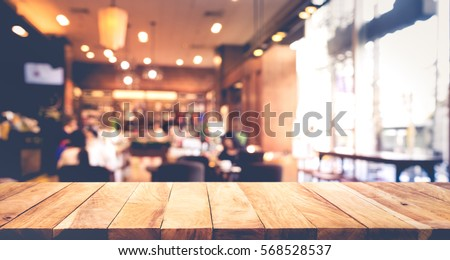 Wood table top with blur of people in coffee shop or (cafe,restaurant )background.For montage product display or design key visual layout #568528537
