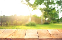 Wood table top with fence and grass in garden background.For  create product display or design key visual layout
