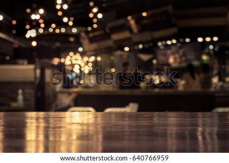 Wood table top with reflect on blur of lighting in night cafe,restaurant background/selective focus. #640766959