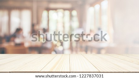 Wood table top with Restaurant cafe or coffee shop interior with people abstract defocused blur background