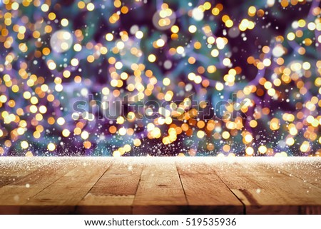 Wood table top with snow and bokeh from decorative light on Christmas tree in background - can be used for display or montage your products