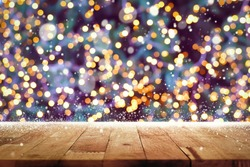 Wood table top with snow and decorative light bokeh on Christmas tree at night in background - can be used for display or montage your products