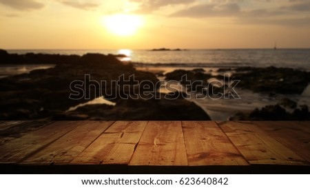 Wood table top with the background blurred rocks and the sea before sunset.. - For product display and advertising and promotional purposes.
