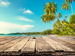 Wood table with blurred sea and coconut tree background