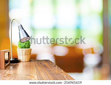 Wood table with lamp and picture frame at blurred garden cafe background