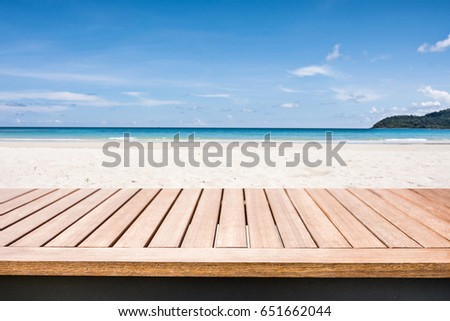 wood terrace over blue sea and tropical island beach background for outdoor advertising mock-up. #651662044